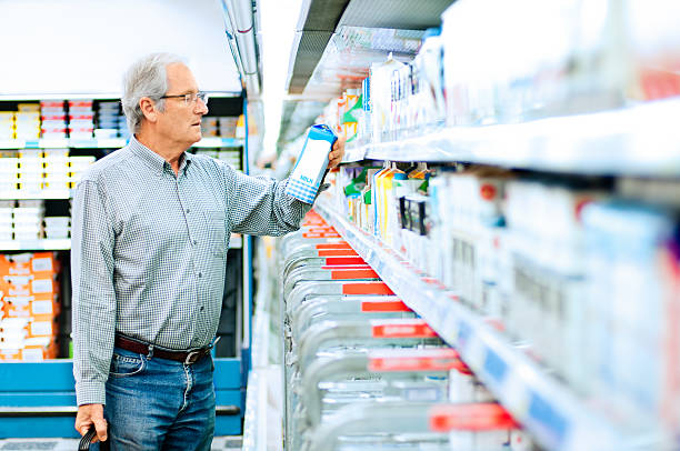 senior man shopping in supermarket - nutrition label stock photos and pictures