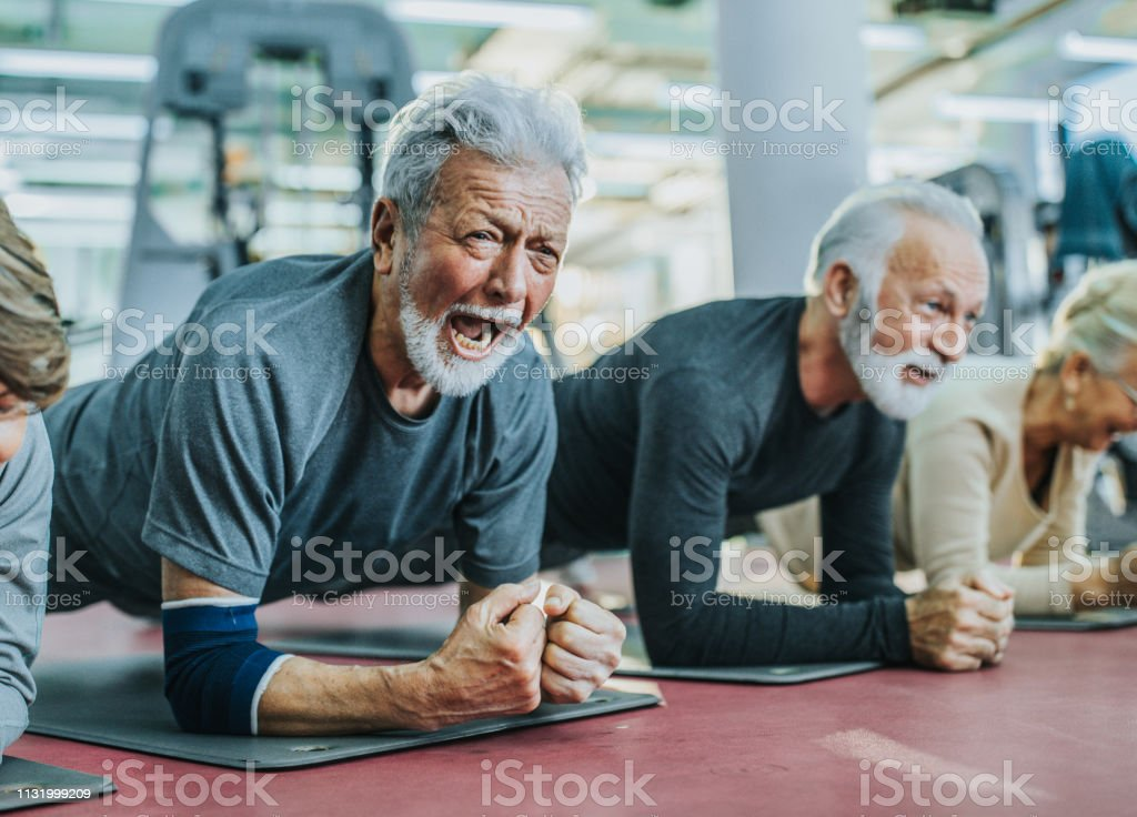 Group of active seniors exercising strength in plank position in a...