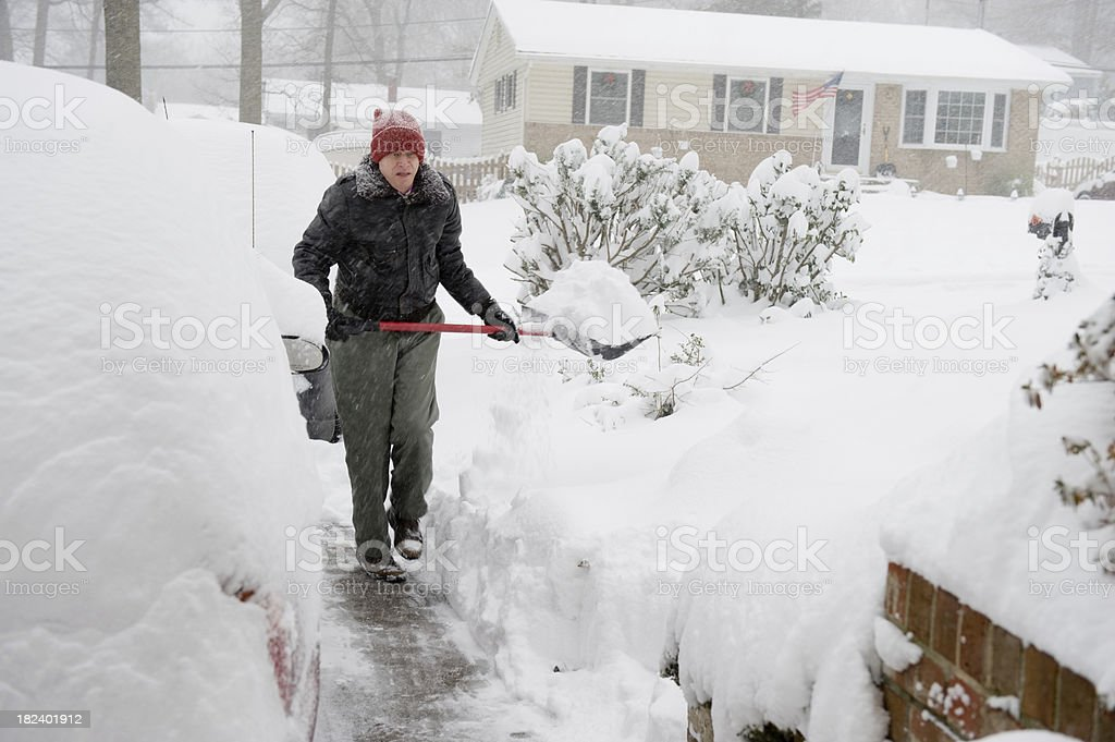 Senior Man Shoveling Snow in Suburbia During Storm stock photo
