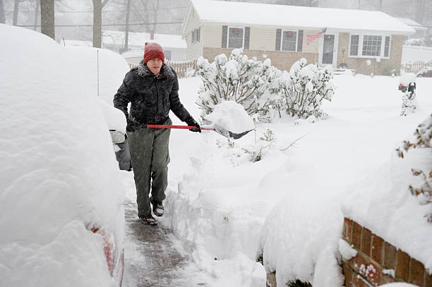 Senior Man Shoveling Snow in Suburbia During Storm stock photo