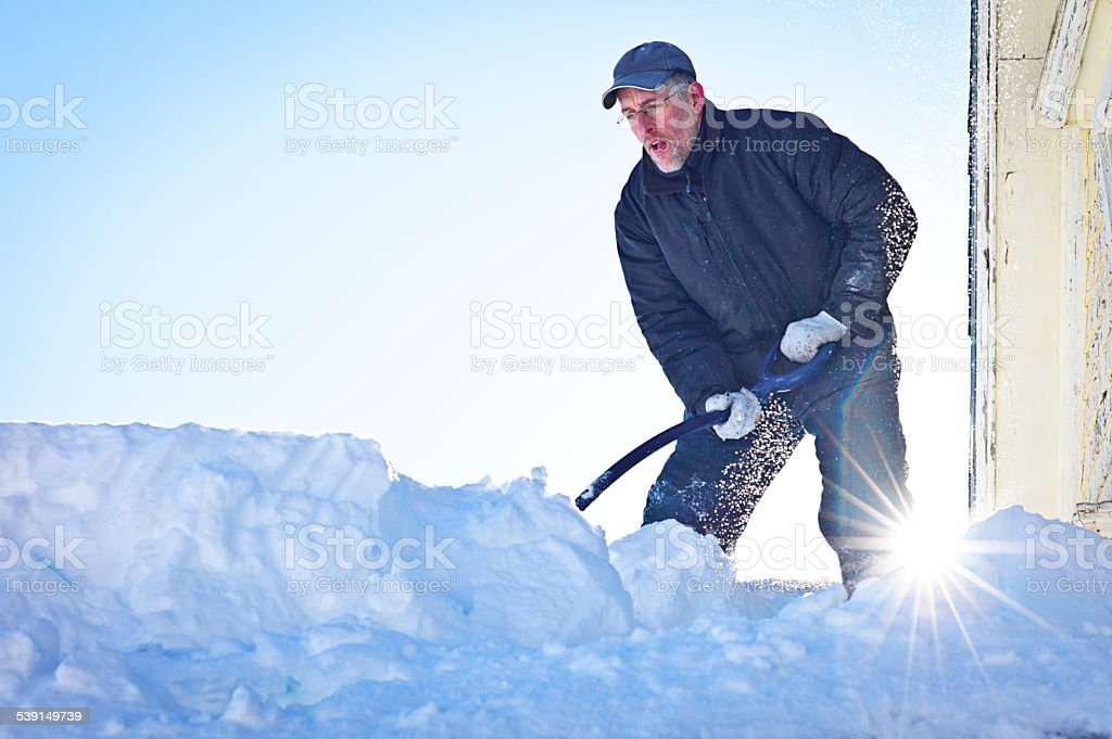 Senior Man Shovels Snow from a Roof Top. stock photo