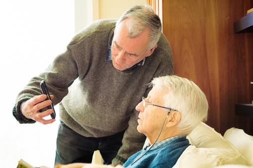Senior man showing his friend media on mobile phone