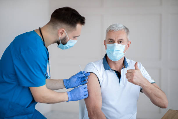 Senior man showing thumb up gesture while being immunized against coronavirus at hospital during his visit to doctor stock photo