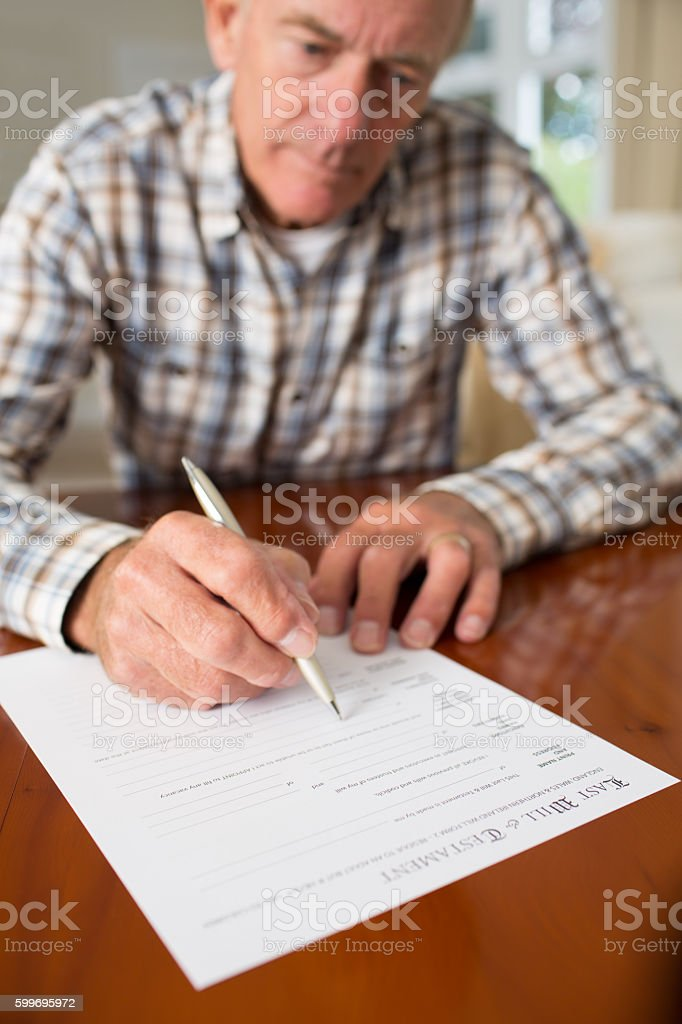 Senior Man Signing Last Will And Testament At Home stock photo