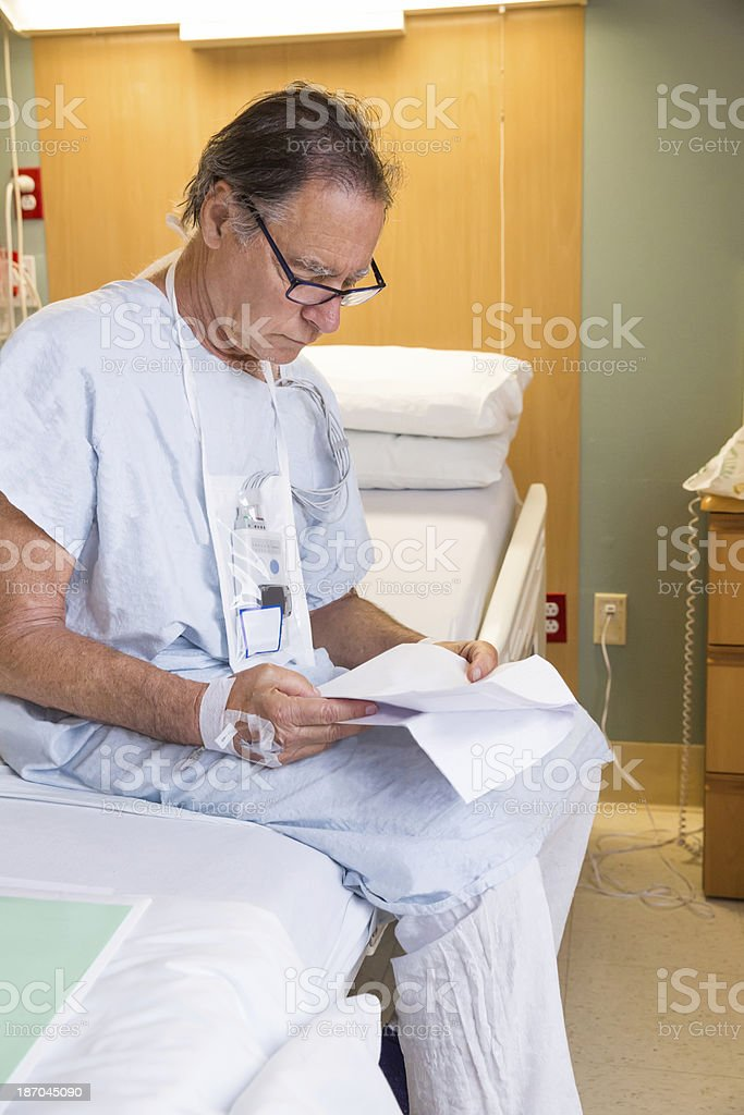 Senior man sits on his hospital bed reading information royalty-free stock photo