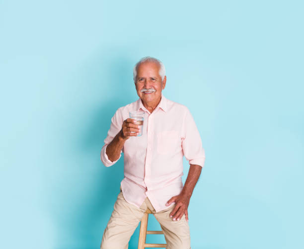 Senior man sitting and holding glass of water stock photo