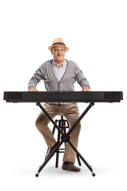 Senior man sitting and playing a keyboard Full length portrait of a senior man sitting and playing a keyboard isolated on white background keyboard player stock pictures, royalty-free photos & images