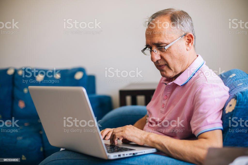 Último homem sentado em casa usando laptop - Foto de stock de 60 Anos royalty-free