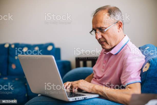 Foto de Último Homem Sentado Em Casa Usando Laptop e mais fotos de stock de 60 Anos