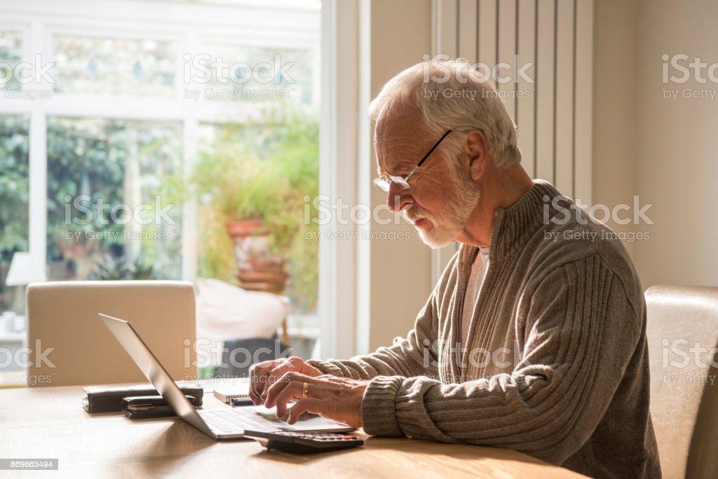 Senior man sitting at home using laptop wearing glasses stock photo