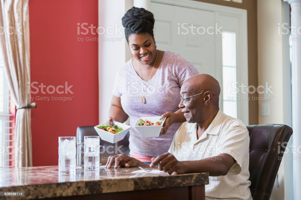 Senior man sitting at table, adult daughter serving food stock photo