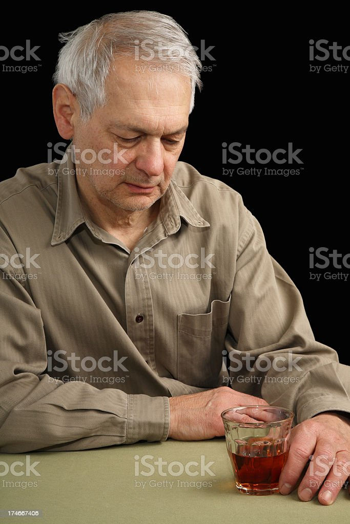 Senior man sitting at table in depressed state with cocktail royalty-free stock photo