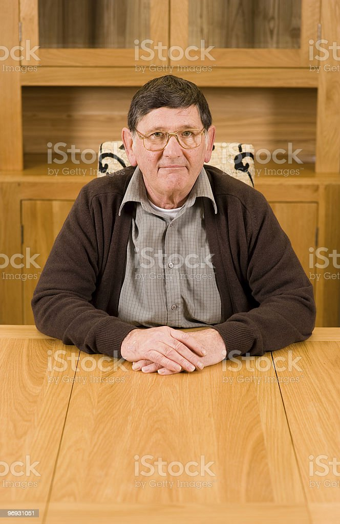 Senior man sitting at table with copyspace below royalty-free stock photo