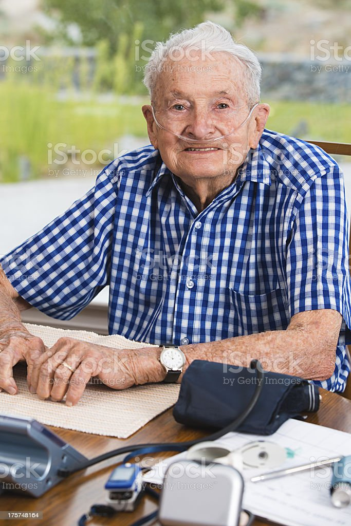 Senior man sitting at the table filled with medical equipment stock photo