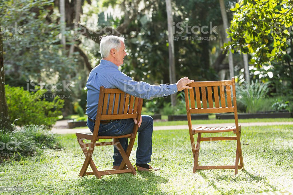 Senior man sitting beside an empty chair stock photo