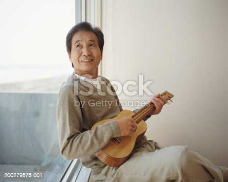 istock Senior man sitting by window playing ukelele, looking up 200279575-001