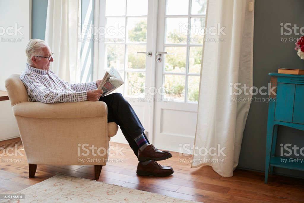 Senior man sitting in an armchair reading newspaper at home stock photo