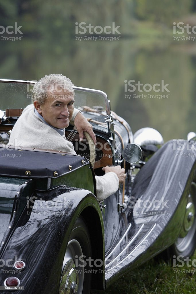 Senior man sitting in antique car royalty-free stock photo