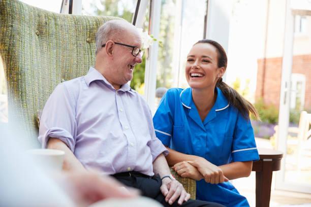senior man sitting in chair and talking with nurse in retirement home - uomo nostalgia foto e immagini stock