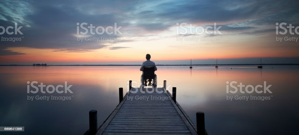 Senior man sitting in wheelchair at the end of lakeside jetty watching majestic cloudscape at dusk stock photo