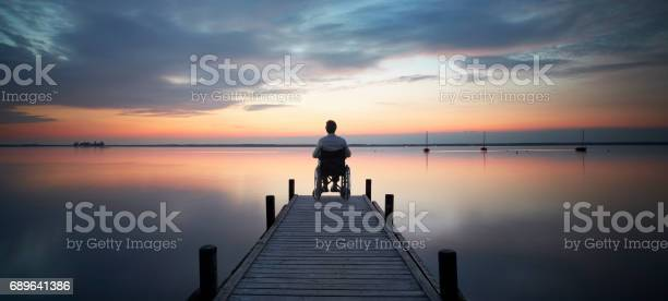 Photo of Senior man sitting in wheelchair at the end of lakeside jetty watching majestic cloudscape at dusk