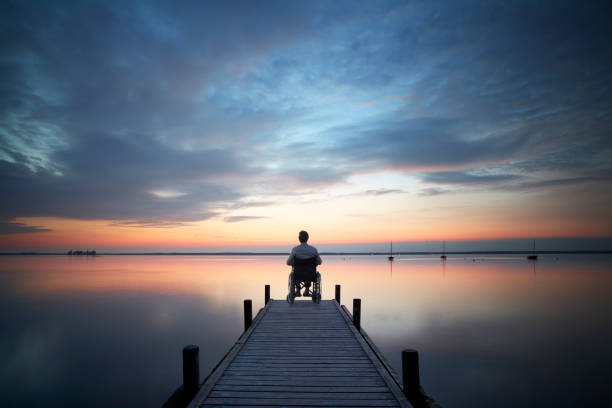 Senior man sitting in wheelchair on jetty at sunset stock photo