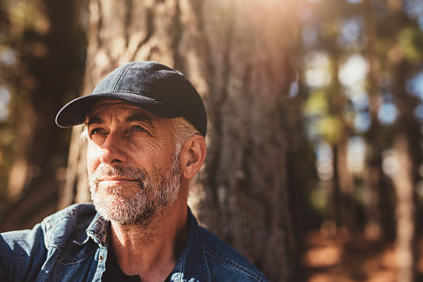 Senior man sitting in woods on a summer day stock photo