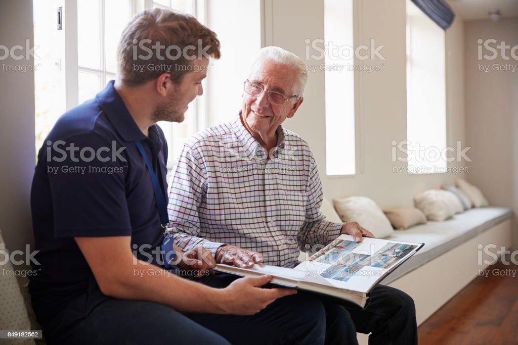 Senior hombre sentado mirando el álbum de fotos con enfermero - foto de stock