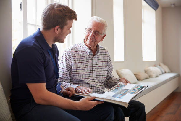 Senior man sitting looking at photo album  with male nurse - foto stock