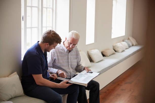 senior man zit kijken naar fotoalbum met verpleger - senior fotoboek stockfoto's en -beelden