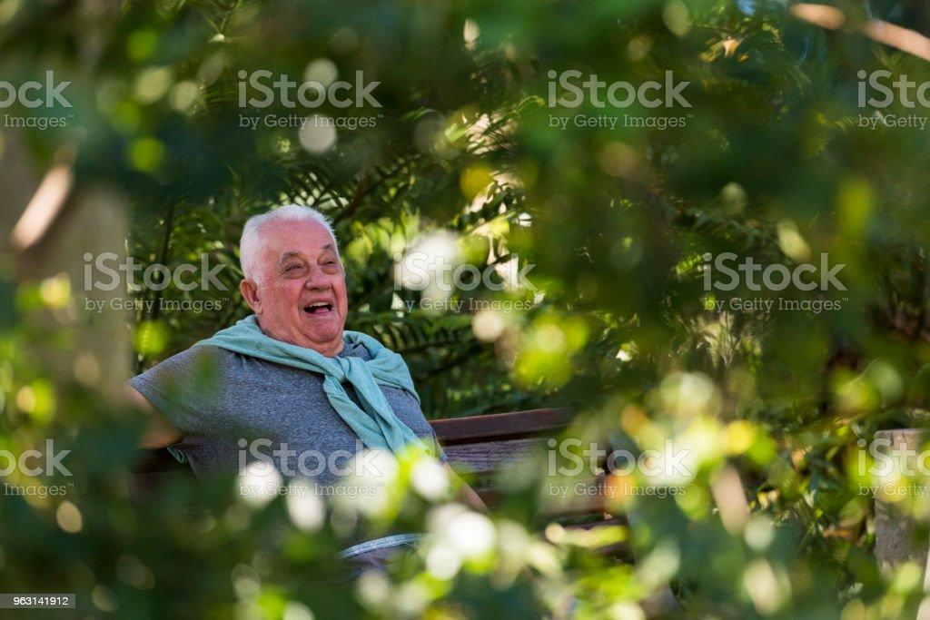 Äldre man som sitter på en bänk utomhus - Royaltyfri 60-64 år Bildbanksbilder