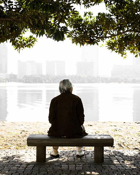 Senior Man Sitting on a Park Bench stock photo