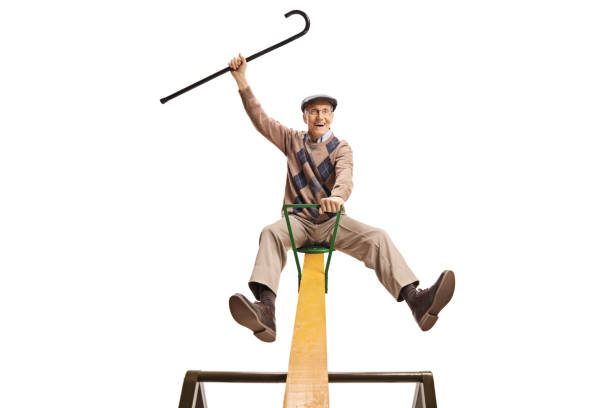 Senior man sitting on a seesaw and holding a cane up stock photo