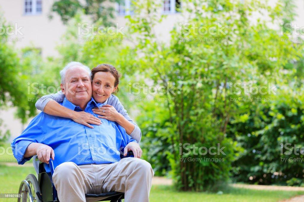 Senior man sitting on a wheelchair with caregiver stock photo