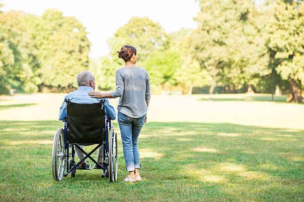 senior man sitting on a wheelchair with caregiver - wheelchair stock photos and pictures