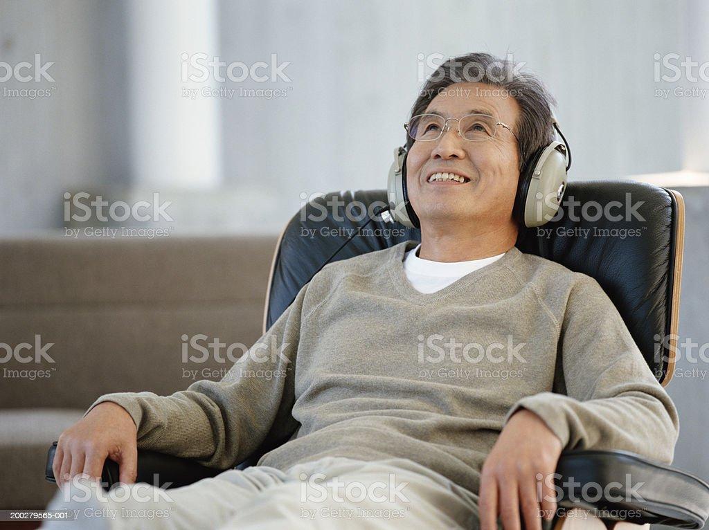 Senior man sitting on armchair wearing headphones, smiling stock photo