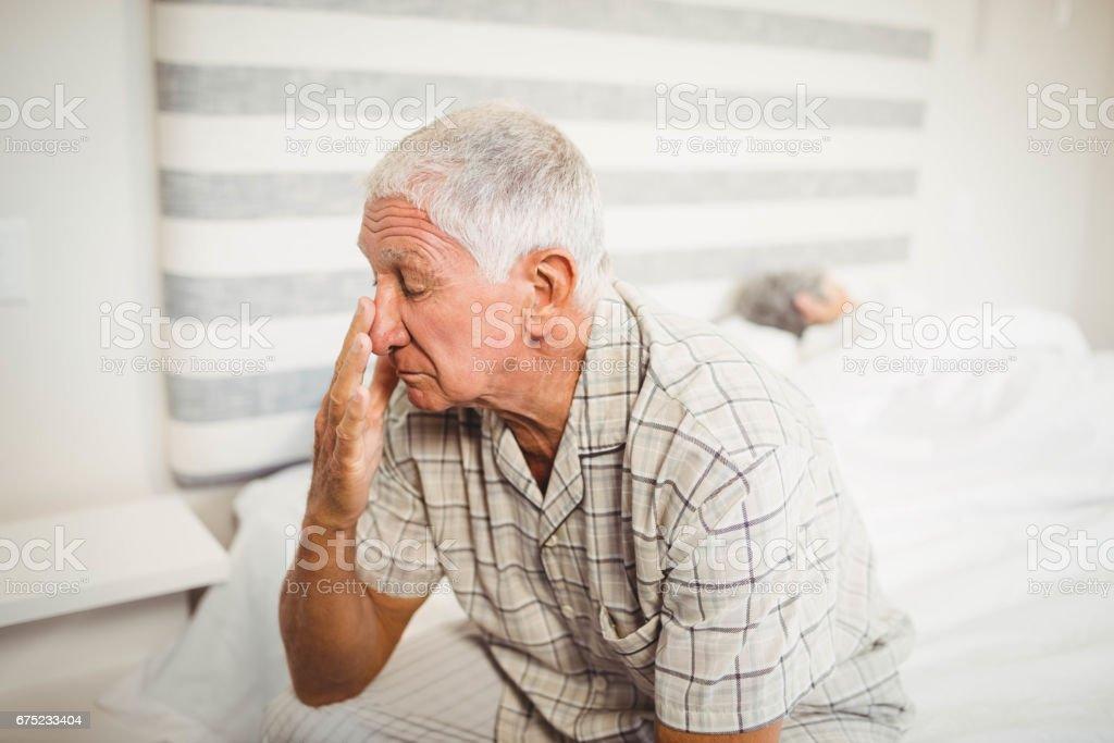 Senior man sitting on bed royalty-free stock photo