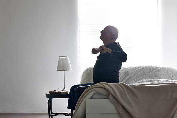 Sênior homem sentado na cama, Alongando seus braços - foto de acervo