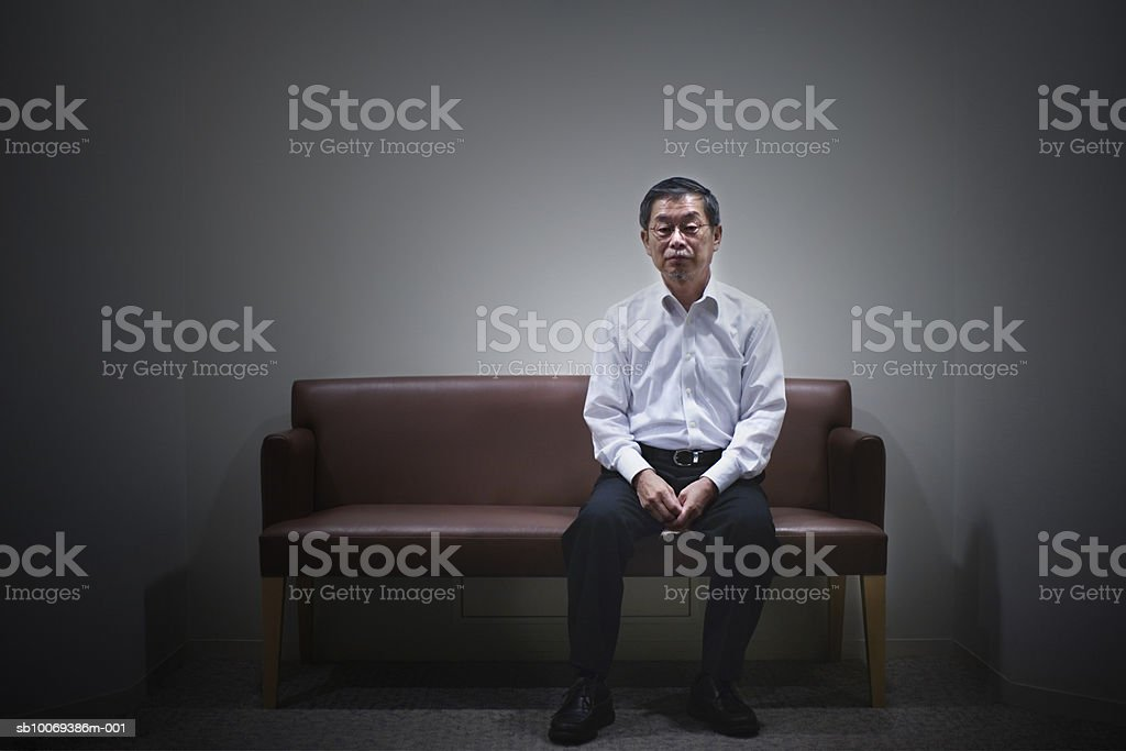Senior man sitting on sofa, portrait 免版稅 stock photo
