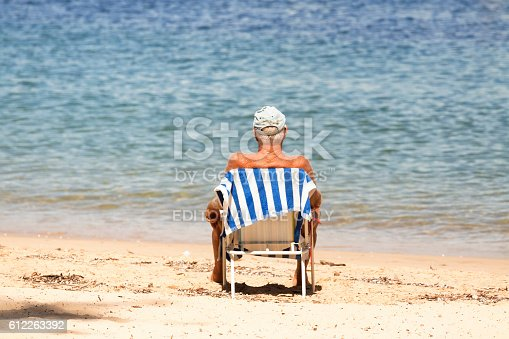 621898406istockphoto Senior man sitting on the beach after swim, copy space 612263392