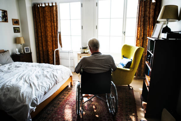 senior man sitting on the wheelchair alone - nursing home zdjęcia i obrazy z banku zdjęć