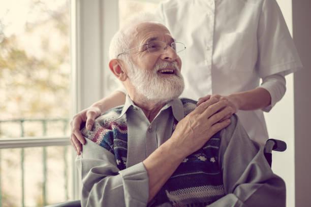 starszy mężczyzna siedzący na wózku inwalidzkim, śmiejąc się i trzymając za rękę pielęgniarkę - dojrzały zdjęcia i obrazy z banku zdjęć
