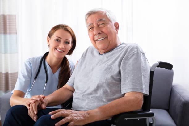 senior mann sitzt im rollstuhl mit weiblich-krankenschwester - hospiz stock-fotos und bilder