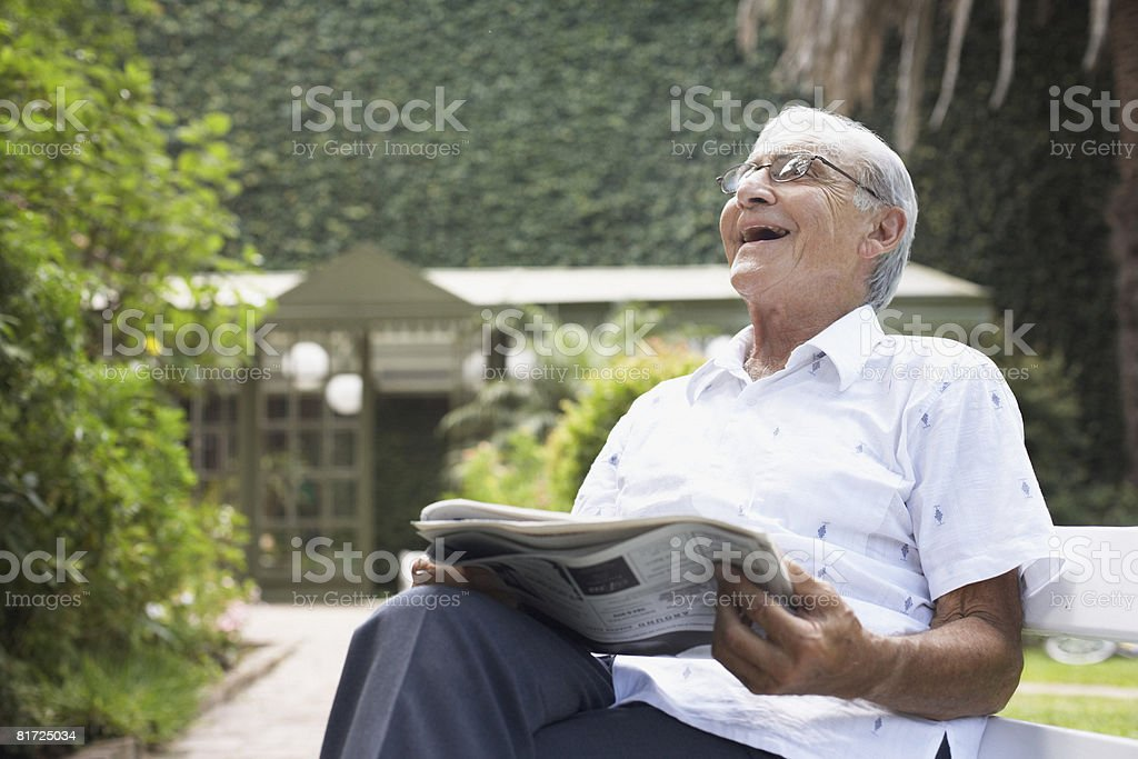 Senior man sitting outdoors with newspaper laughing stock photo