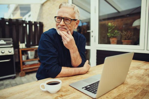 senior man sitting outside drinking coffee and using a laptop - casa reforma imagens e fotografias de stock