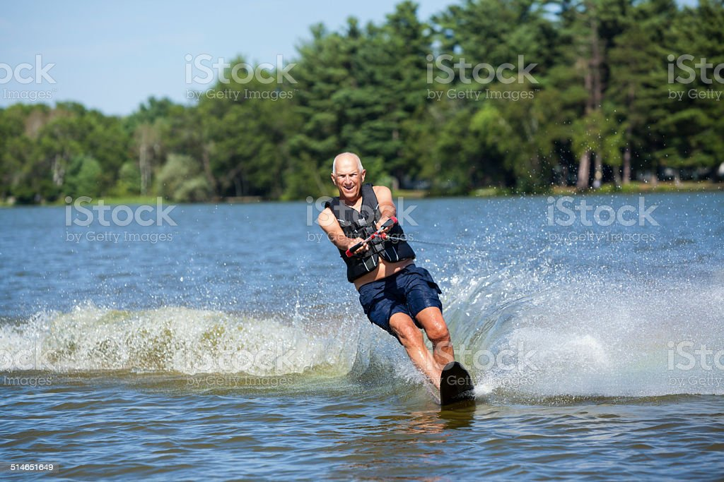 Senior Man Slalom Water Skiing on Summer Lake stock photo