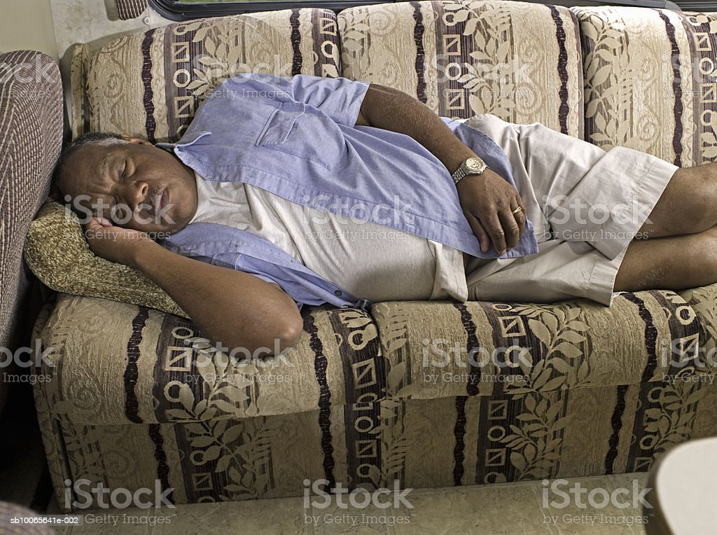 Senior man sleeping on sofa  in motorhome royalty-free stock photo