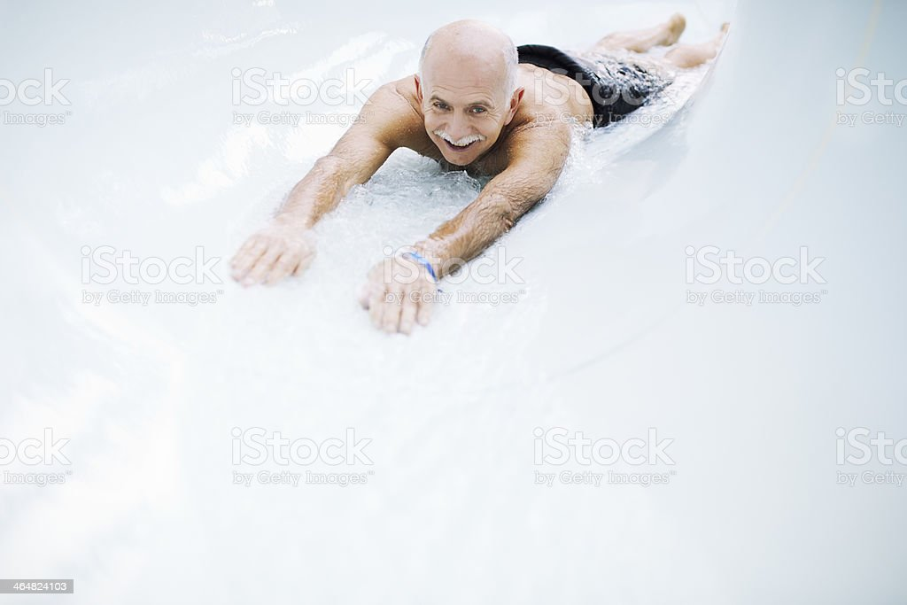 Senior Man Sliding Down Water Slide stock photo