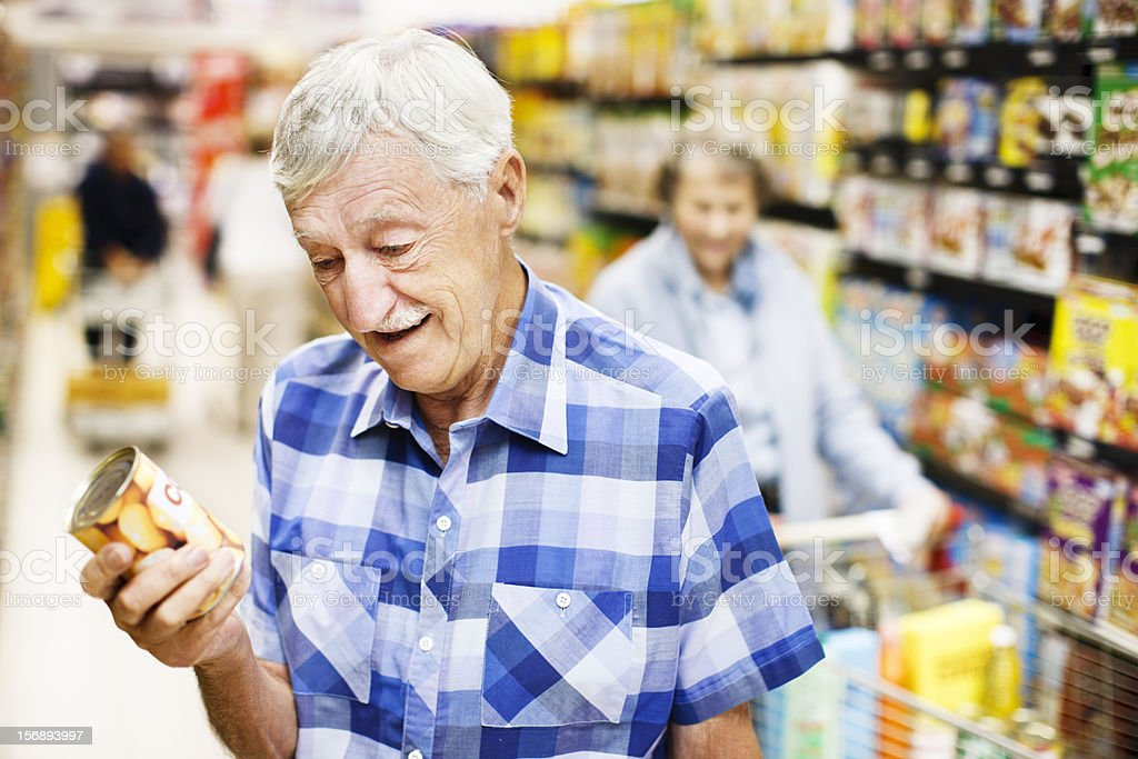 Senior man smiles, finding his favorite canned food in supermarket stock photo