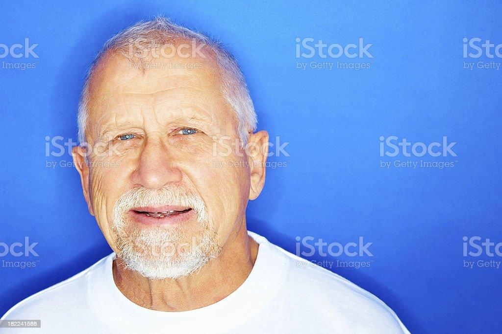 Senior man smiling against blue background royalty-free stock photo